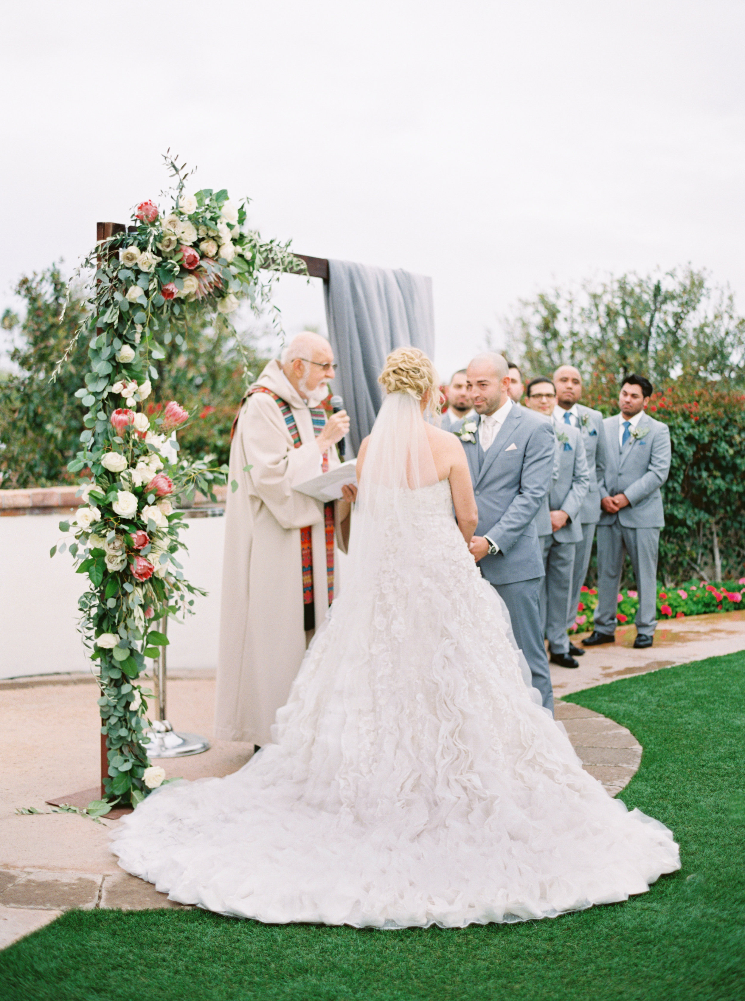 29 bride groom ceremony priest wedding ceremony outdoor wedding rain on wedding day floral arch wedding arch Life Design Events photos by Melissa Jill Photography.jpg