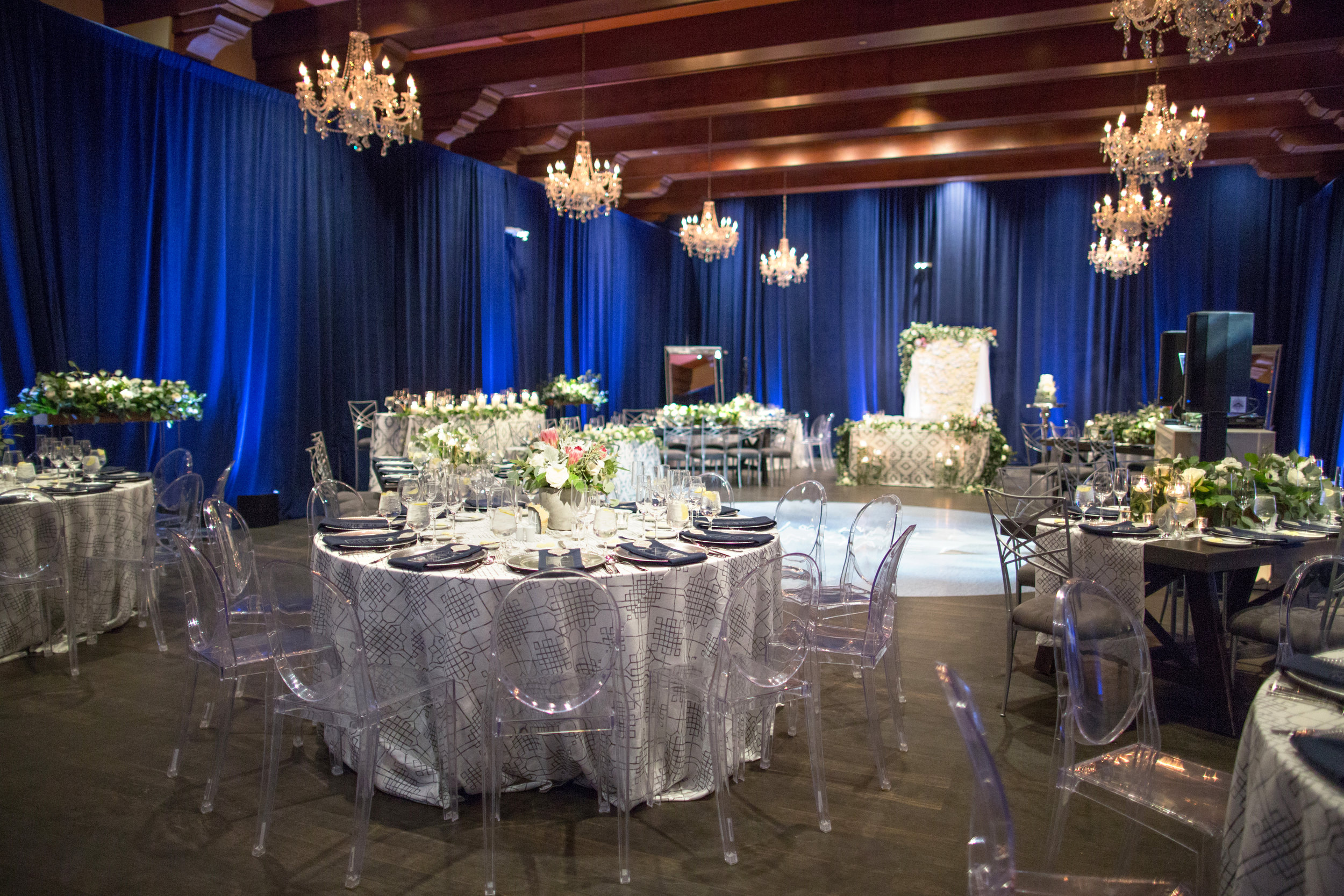 40 wedding reception blue velvet room chandelier wedding room white wedding flowers custom dance floor hydrangea backdrop clear ghost chair grey linen wedding reception dinner Life Design Events photos by Melissa Jill Photography.jpg