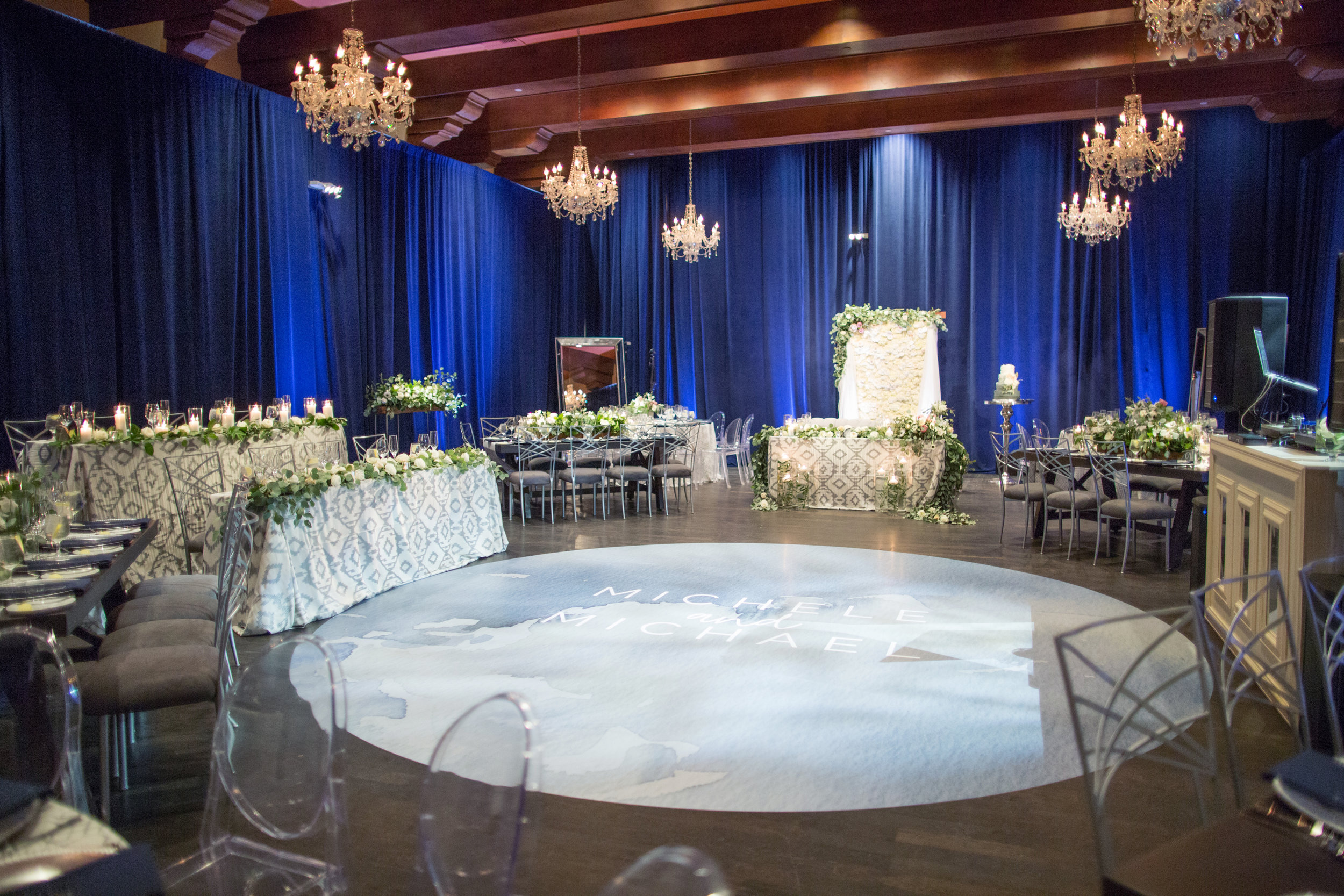 41 wedding reception blue velvet draped walls chandeliers wood beam ceiling custom dance floor decal bride groom name dance floor dinner reception white wedding flowers hydrangea backdrop Life Design Events photos by Melissa Jill Photography.jpg