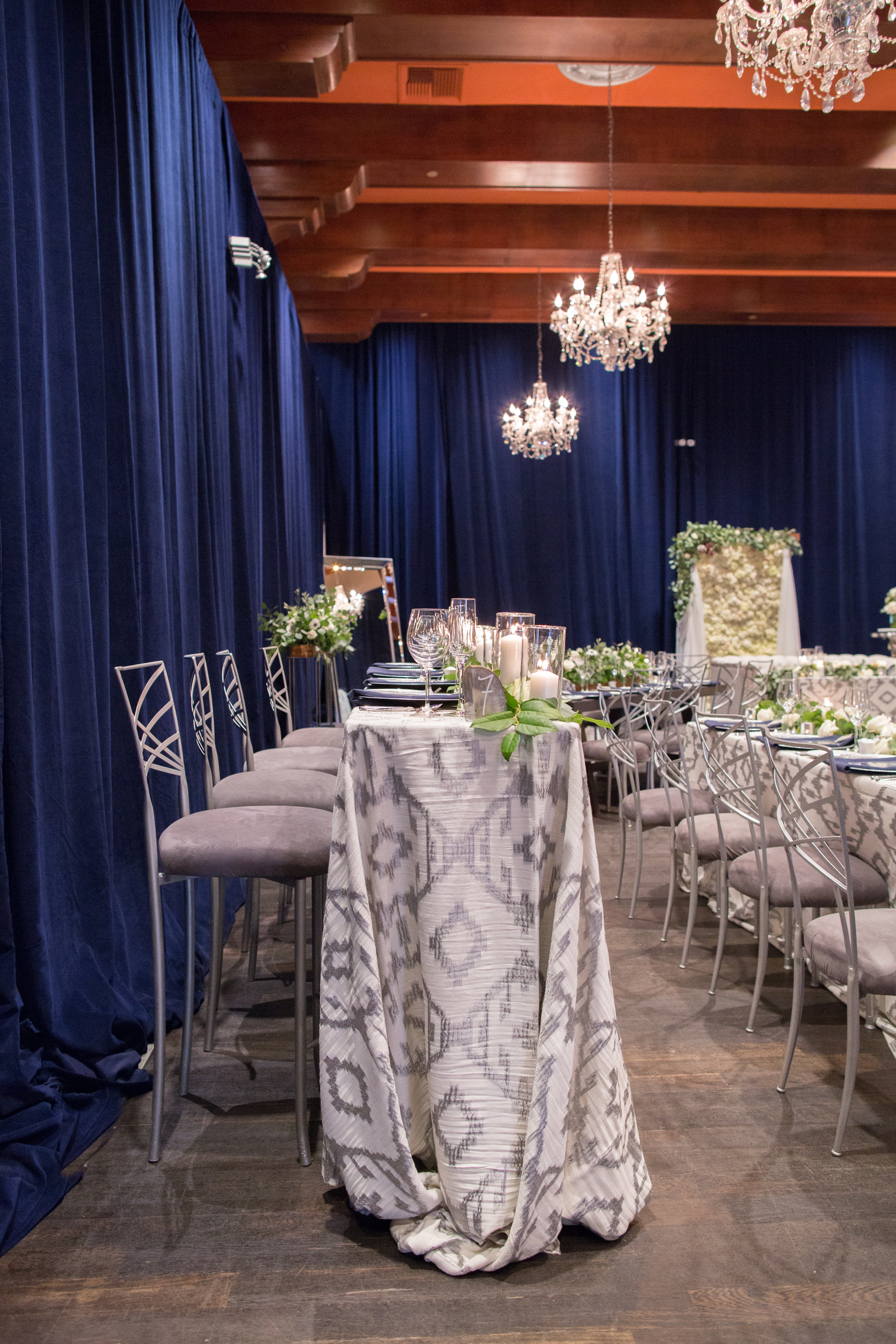 43 wedding reception blue velvet wall dramatic wedding reception raised head table white wedding flowers chandelier on wood beam ceiling Life Design Events photos by Melissa Jill Photography.jpg