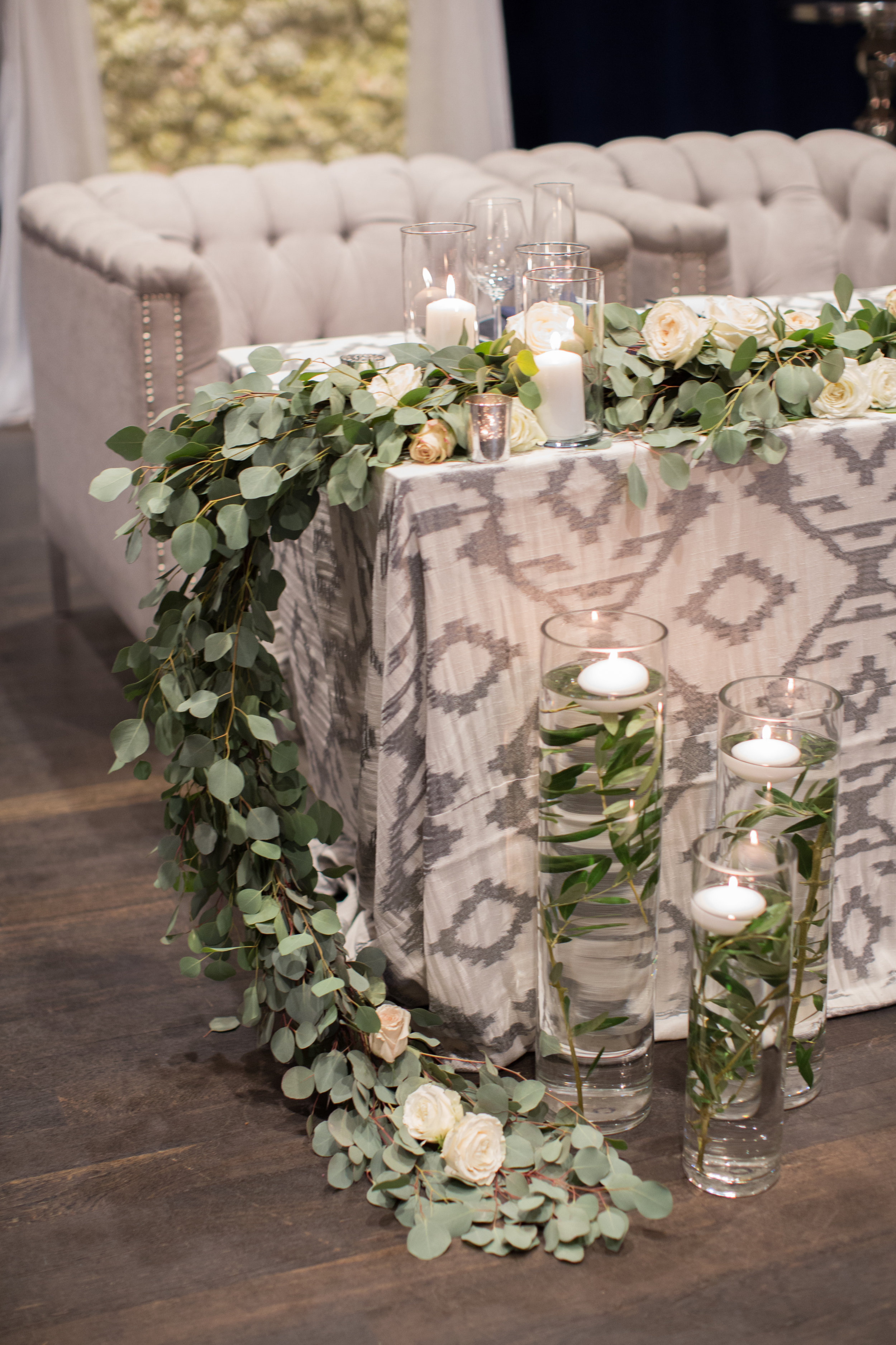 45 sweetheart table comfortable seating bride groom couch floral sweetheart table floating candles white hydrangea backdrop Life Design Events photos by Melissa Jill Photography.jpg