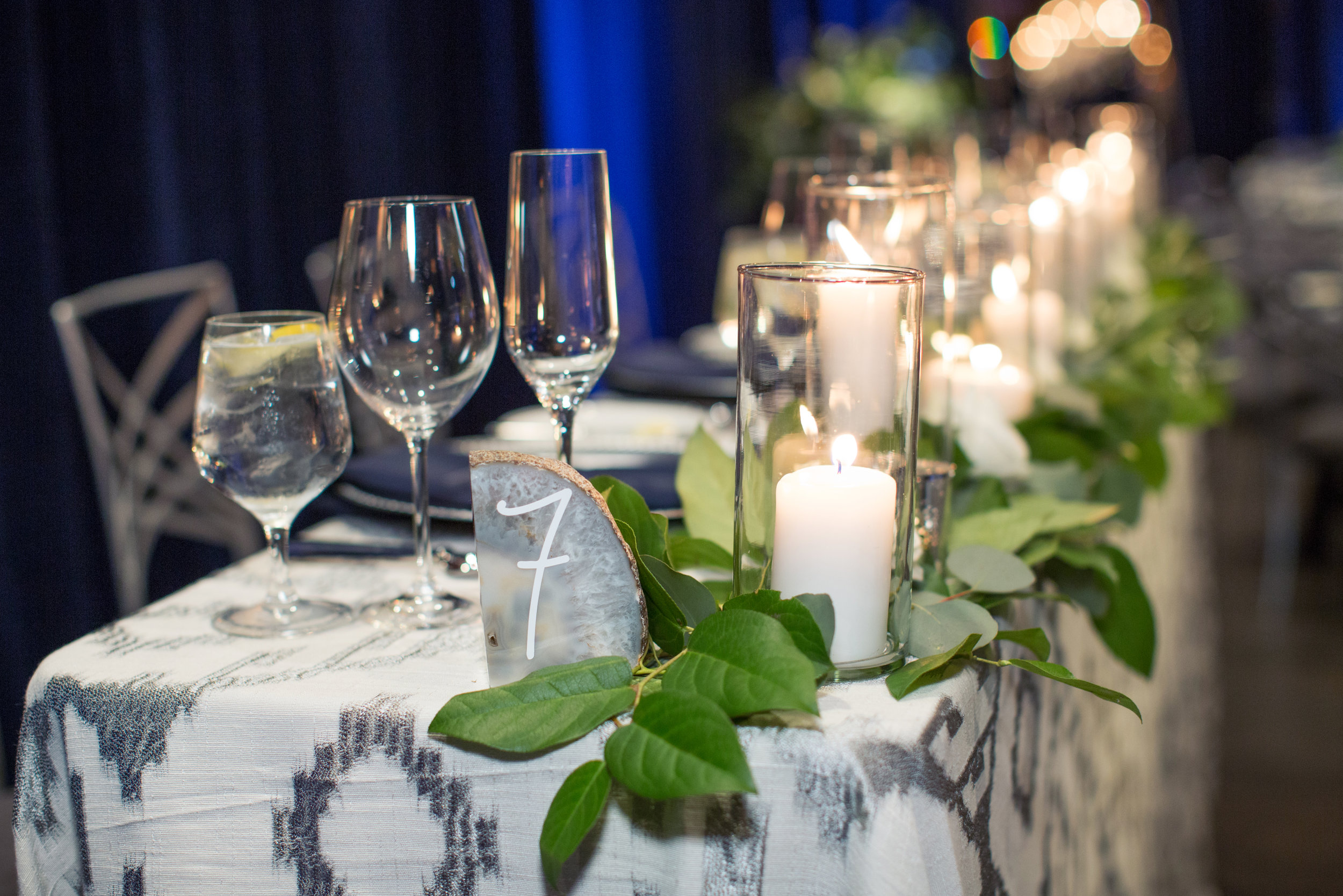 49 wedding reception guest table candlelight flower greenery garland agate slice table number assigned seating wedding reception Life Design Events photos by Melissa Jill Photography.jpg