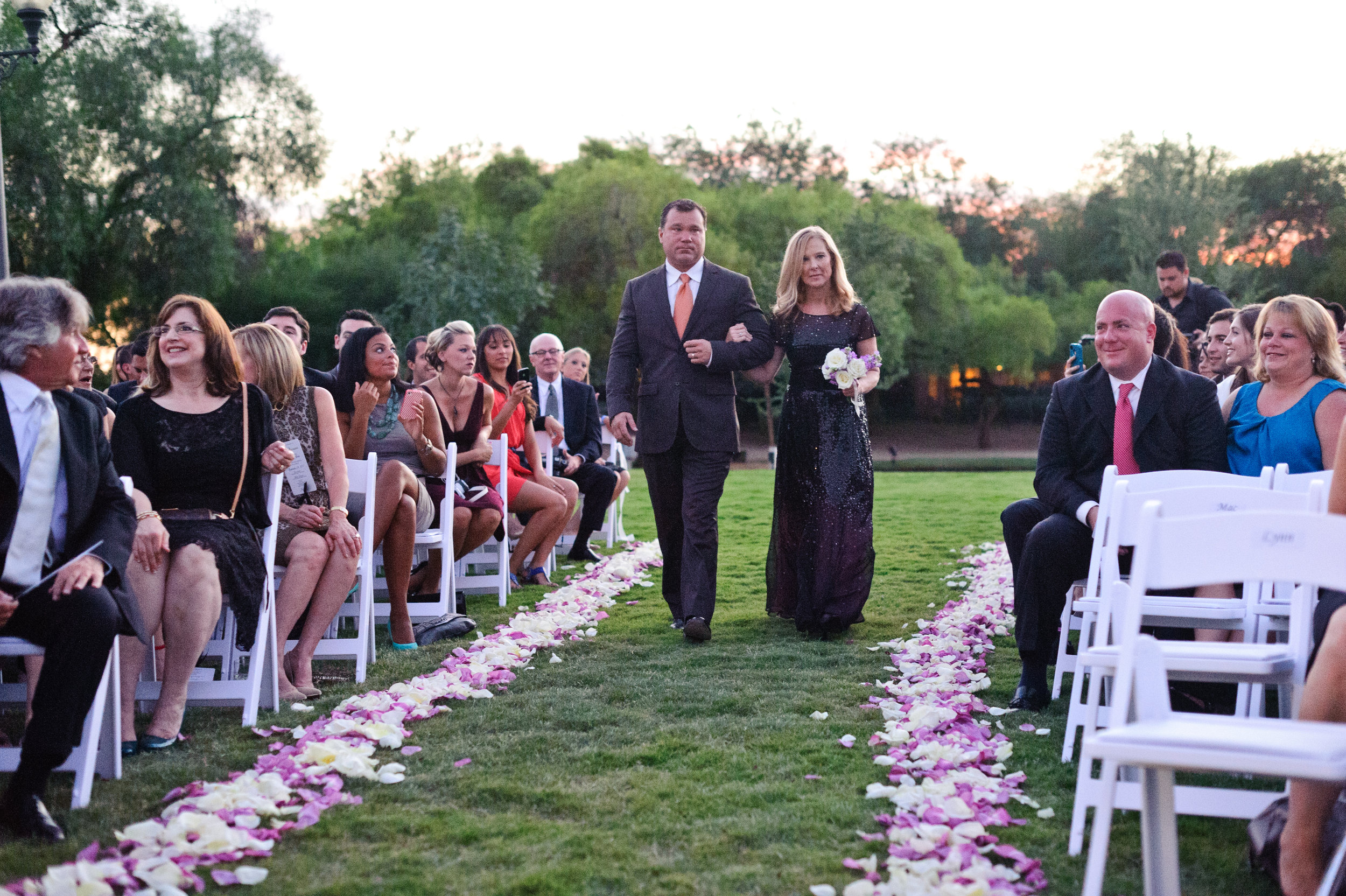 15 bride and groomsmen walking down the aisle spring wedding white wedding chairs purple and white rose petals down the aisle .JPG