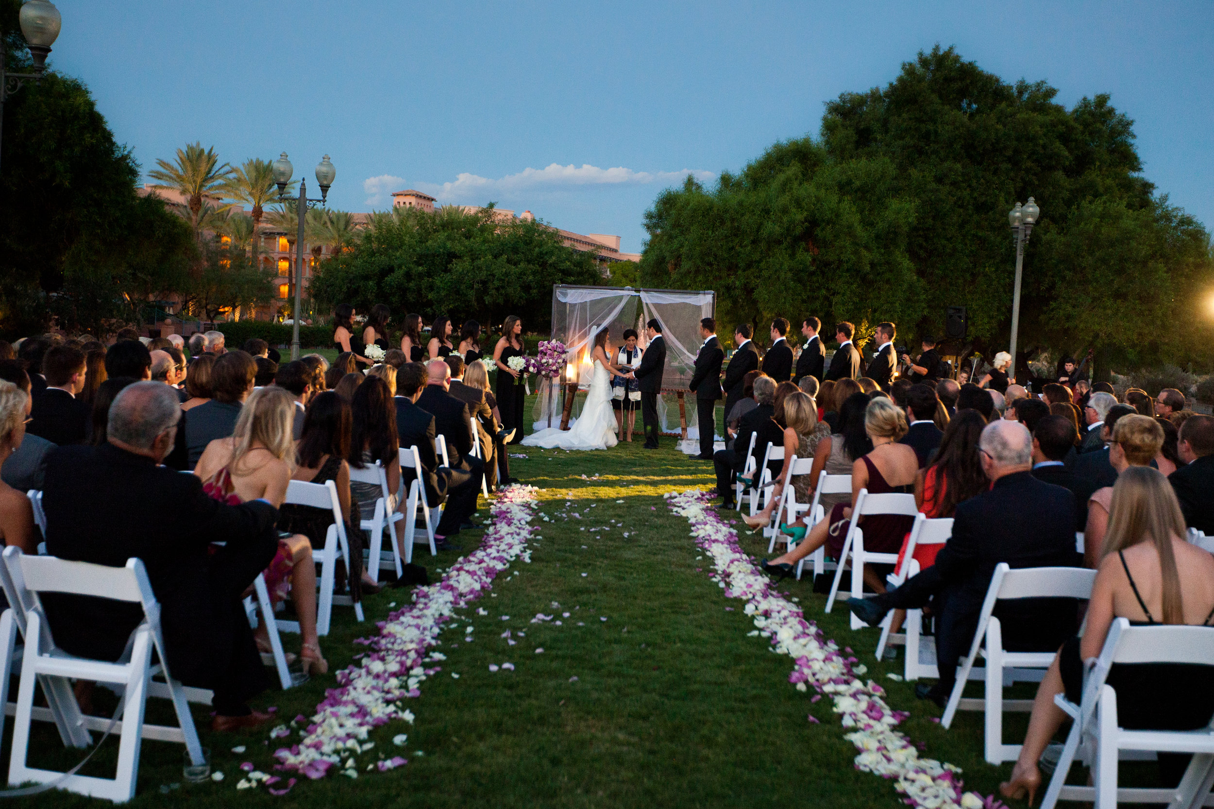 19 white wedding chairs bride and groom at alter purple and white rose petals down aisle ceremony in the evening Sergio Photography Life Design Events.JPG