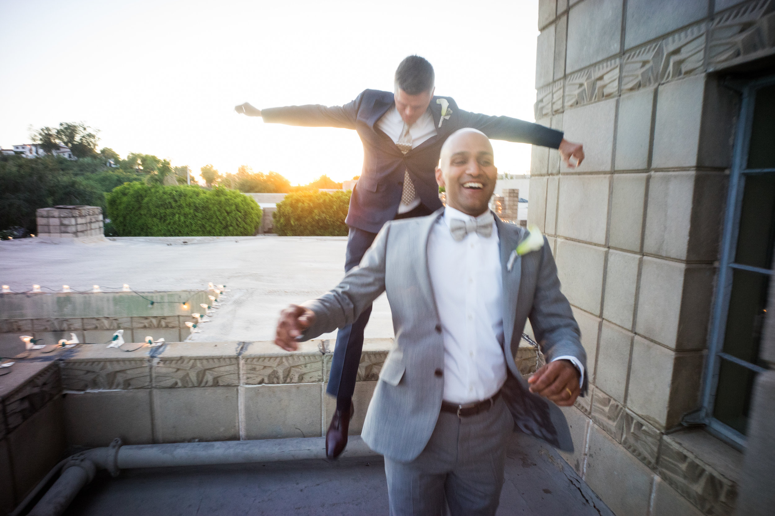 12a excited groom jumping groom laughter laughing groom after ceremony photo two grooms arizona biltmore roof photos just married sunset wedding photos Life Design Events photos by Keith and Melissa Photography.jpg