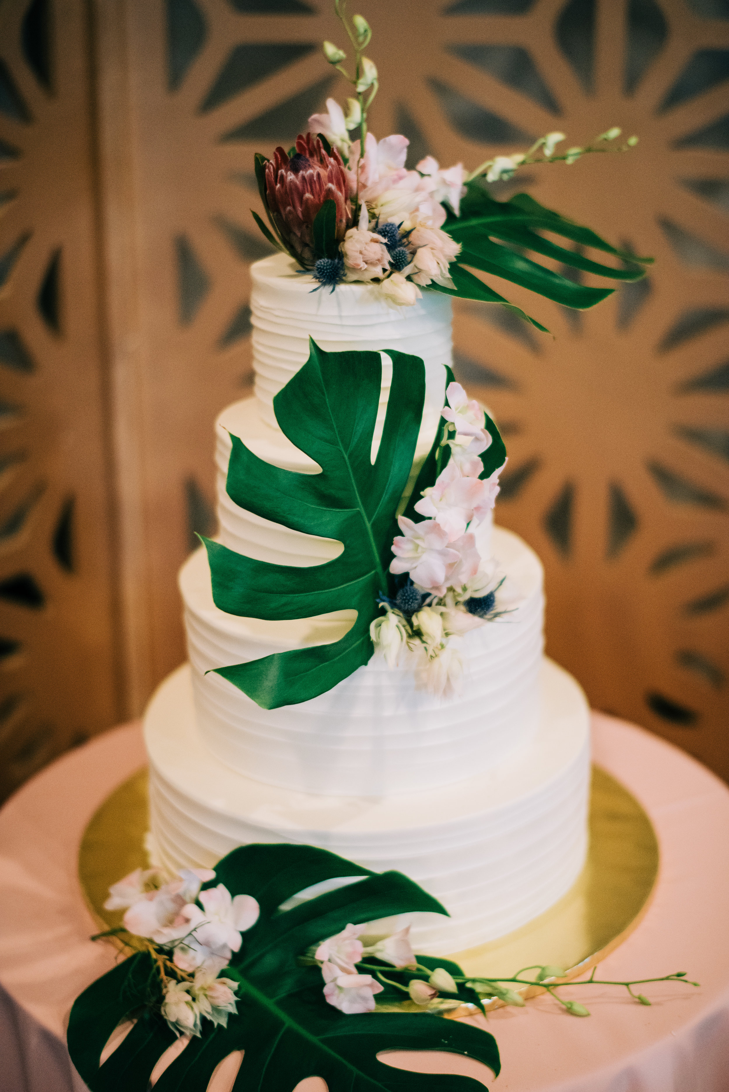30 wedding cake white wedding cake three tier simple wedding cake tropical flower wedding cake tropical leaves protea orchid cake Life Design Events photos by Josh Snyder Photography.jpg