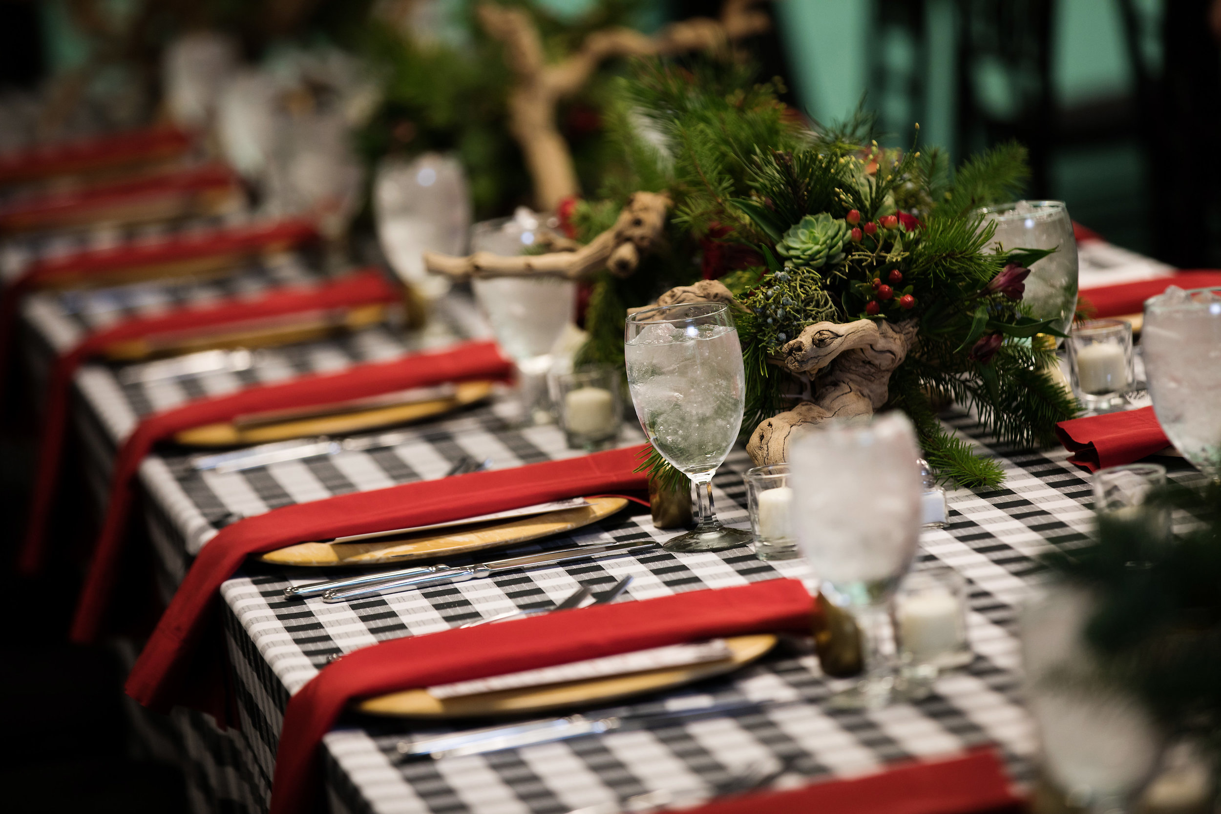 2 red napkins christmas party christmas dinner red and green centerpieces red rose succulent driftwood centerpieces black and white checkered linen family dinner staff dinner Life Design Events photos by Largo Photography.jpg