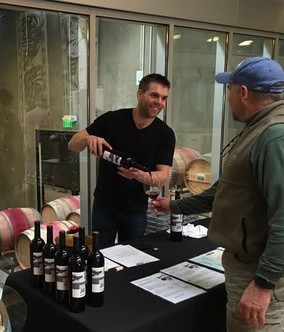 Andrew Januik at Januik/Novelty Hill winery, pouring some wine for a customer.