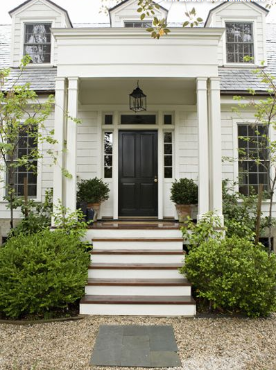Inviting black front door and two aged pots filled with greenery says welcome..... - image: Gillian Lazanik