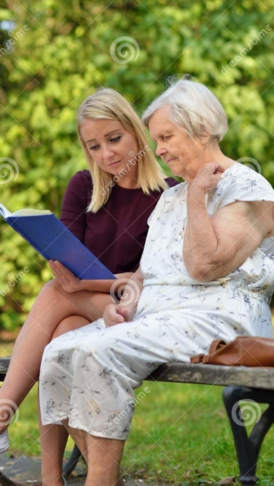 young-woman-reading-book-elderly-woman-women-women-park-78306448.jpg