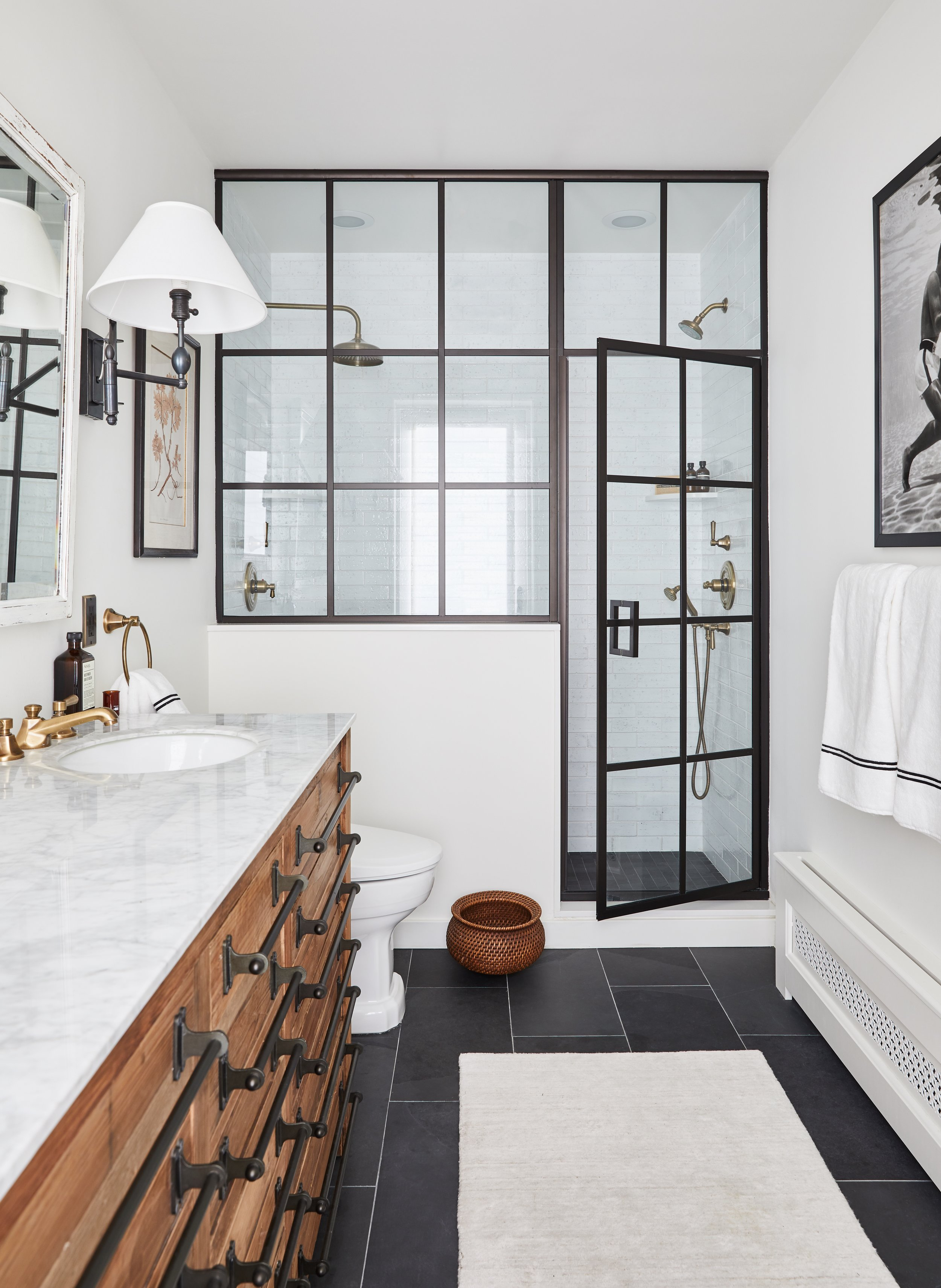 Brooklyn zen with a touch of masculinity was our goal for this Master Bath in Fort Greene Brooklyn that was featured in House Beautiful. Radiant heat makes these slate floors from Stone Source extra toasty and the custom glass shower enclosure steals the show. A reclaimed pine double vanity with Carrara marble from Restoration Furniture and Design gives ample space for storage while adding warmth to this otherwise classic black and white bathroom.