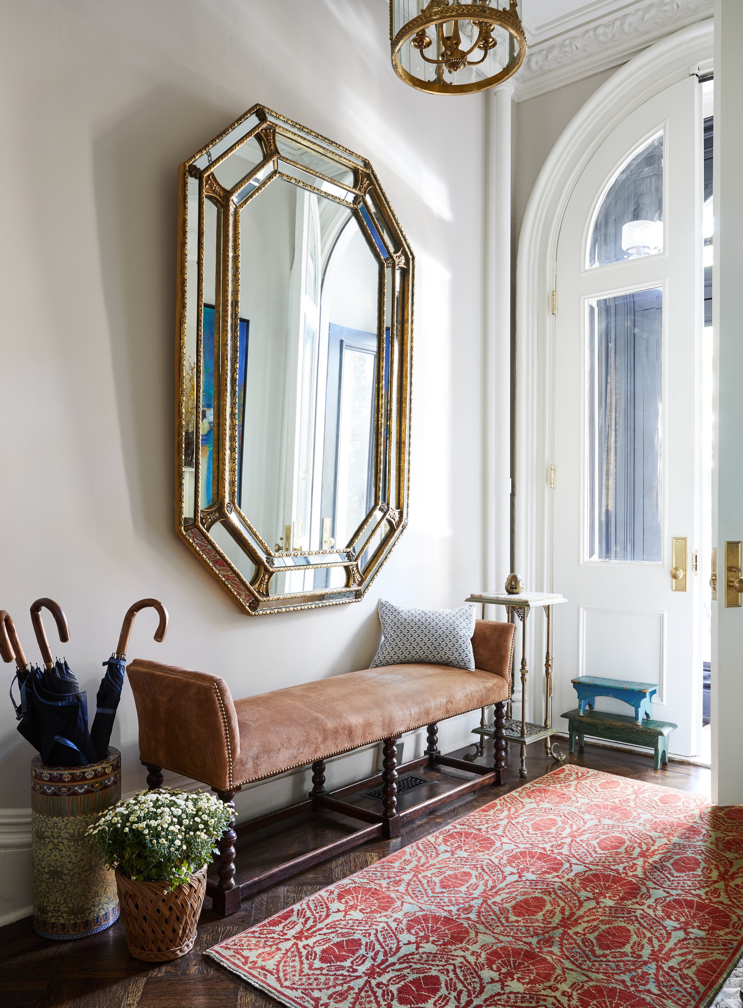 A foyer in a Brooklyn townhouse with an antique oversized gilt mirror from Vidal's, a rug from ABC Carpet, antique hand painted cricket stools, Francesco Maglia Lord Chestnut umbrellas from Mr. Porter in a vintage ceramic stand, a pillow from John Derian, a suede bench with nailheads from John Rosselli, and original mouldings and doors. Antique pendant light and bronze and marble table from Olde Good Things.