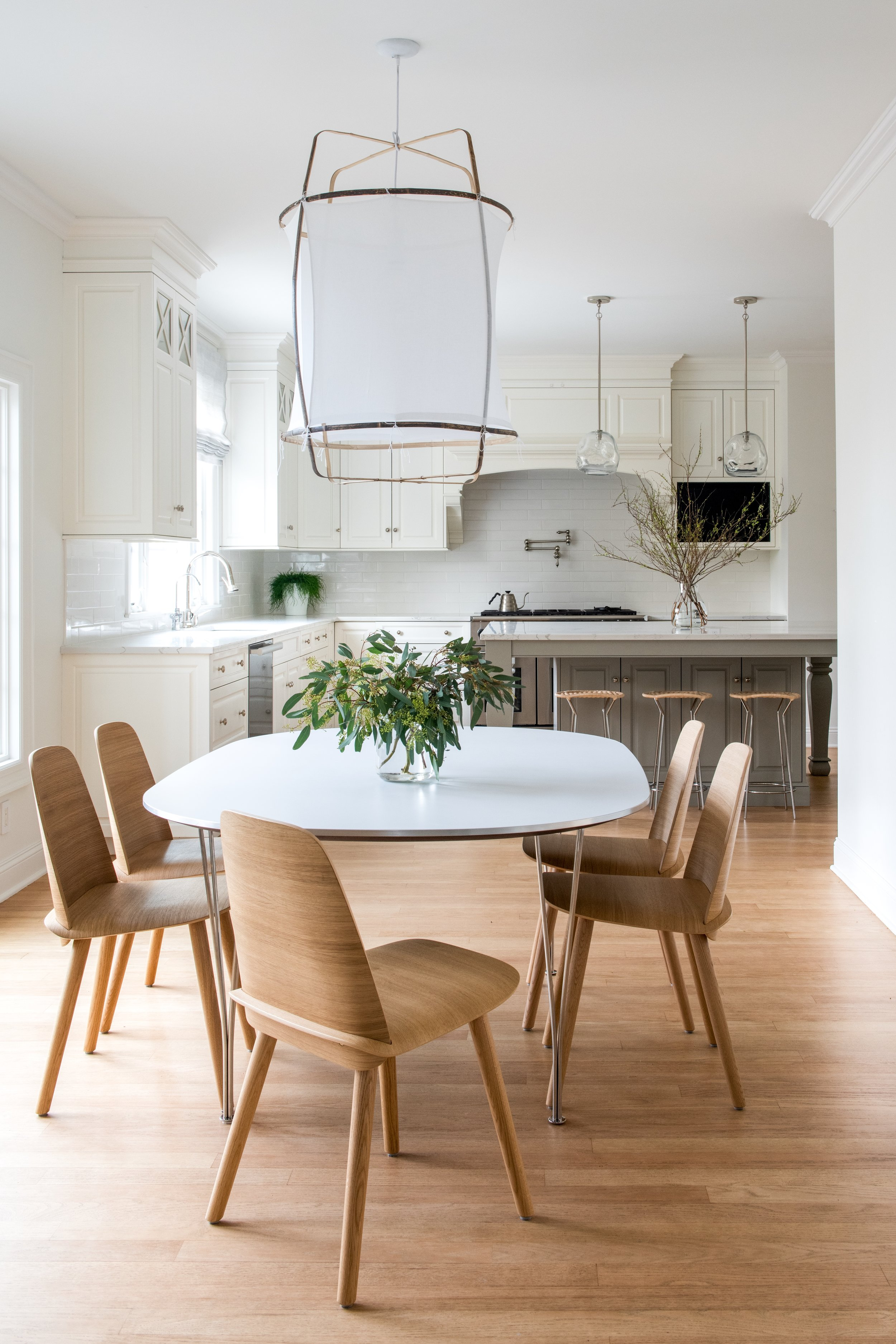 A Ridgewood, New Jersey spec house remodeled to amend architectural proportions and update finishes. The client wanted a clean, soft, neutral aesthetic as a counterpoint to her busy daily life. Child-friendly quartz countertops in a white and grey veined patten replace dark granite to lighten and brighten the space with new deck mounted Waterworks fixtures. The dark and busy backsplash was removed and a clean and bright Waterworks ceramic tile was installed in an a-typical layout for the smallest design detail. All existing appliances and cabinetry were kept, but the dark wood center island was painted in Farrow & Ball's Hardwick White to bring in the grey the client loves. The Bar stools in a woven wicker sourced from Italy create extra seating in the heart of the home. A new informal eating space was created for day to day family meals with a Super Elliptical table by Bruno Mathsson and Nerd Chairs from Design Within Reach that sit under an airy linen and bamboo pendant light from Ay Illuminate.