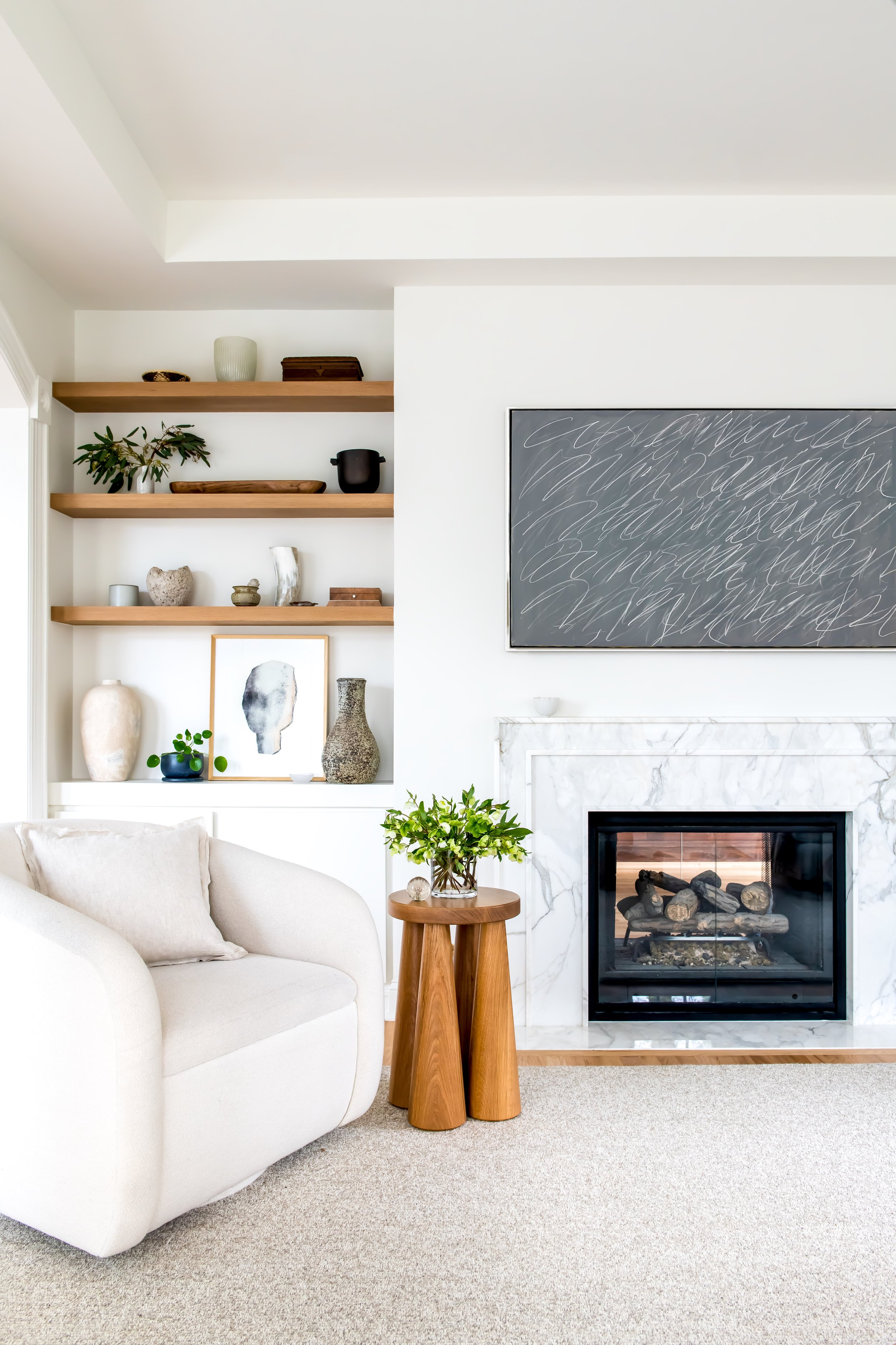 A serene living room layered in neutrals with a custom marble mantel surrounding a double sided firebox painted black under a Samsung Frame TV to display a Cy Twombly piece of art. A custom swivel chair in a Holland & Sherry wool boucle and a sculptural wood side table sourced from 1stdibs sit atop a plush wool rug from Stark Carpet. Custom white washed white oak floating shelves display a collection of beautiful objects including a vintage shagreen box, a horn vessel, and hand made ceramics.