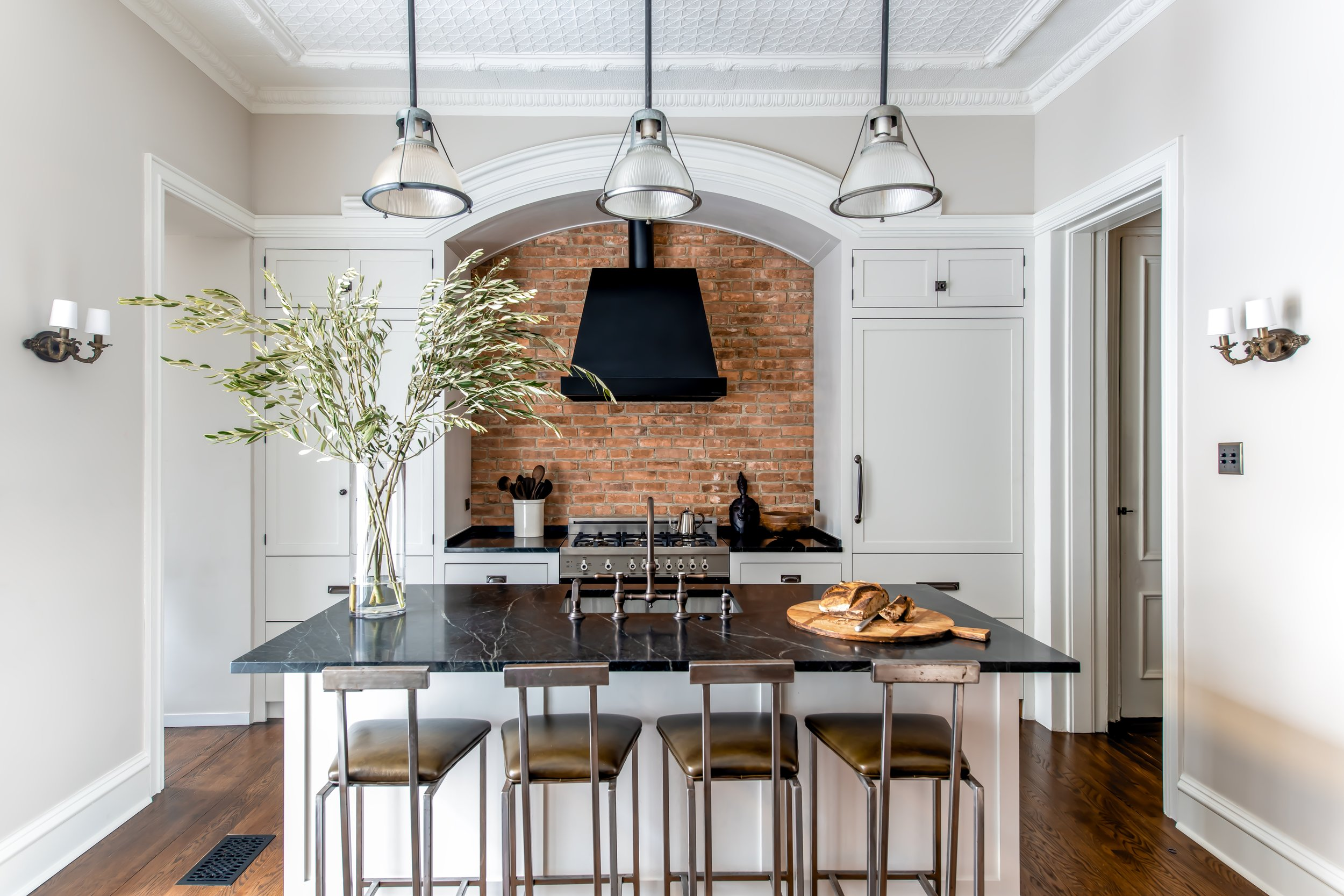 The quintessential Brooklyn kitchen with soaring 13' ceilings decorated in a custom tin design that was hand-pressed on turn of the century equipment with antique rope drop hammers and painted in Benjamin Moore White Dove along with the trim. Custom cabinets painted in Benjamin Moore Silver Satin create the perfect amount of contrast and are finished in Armac Martin hardware. The original brickwork from the 1860s was exposed and repointed to be the feature under a custom arch to compliment the original arched stained glass window that leads out to the terrace and private garden. Both the Sub-Zero refrigerator and Miele dishwasher were hidden behind cabinet panels with the Bertazzoni gas range as the only appliance left exposed. Newport Brass fixtures are deck mounted into the deepest green soapstone countertops. Custom steel chairs in an olive green Dualoy leather provide seating with vintage holophane lights from Olde Good Things to illuminate the large space.