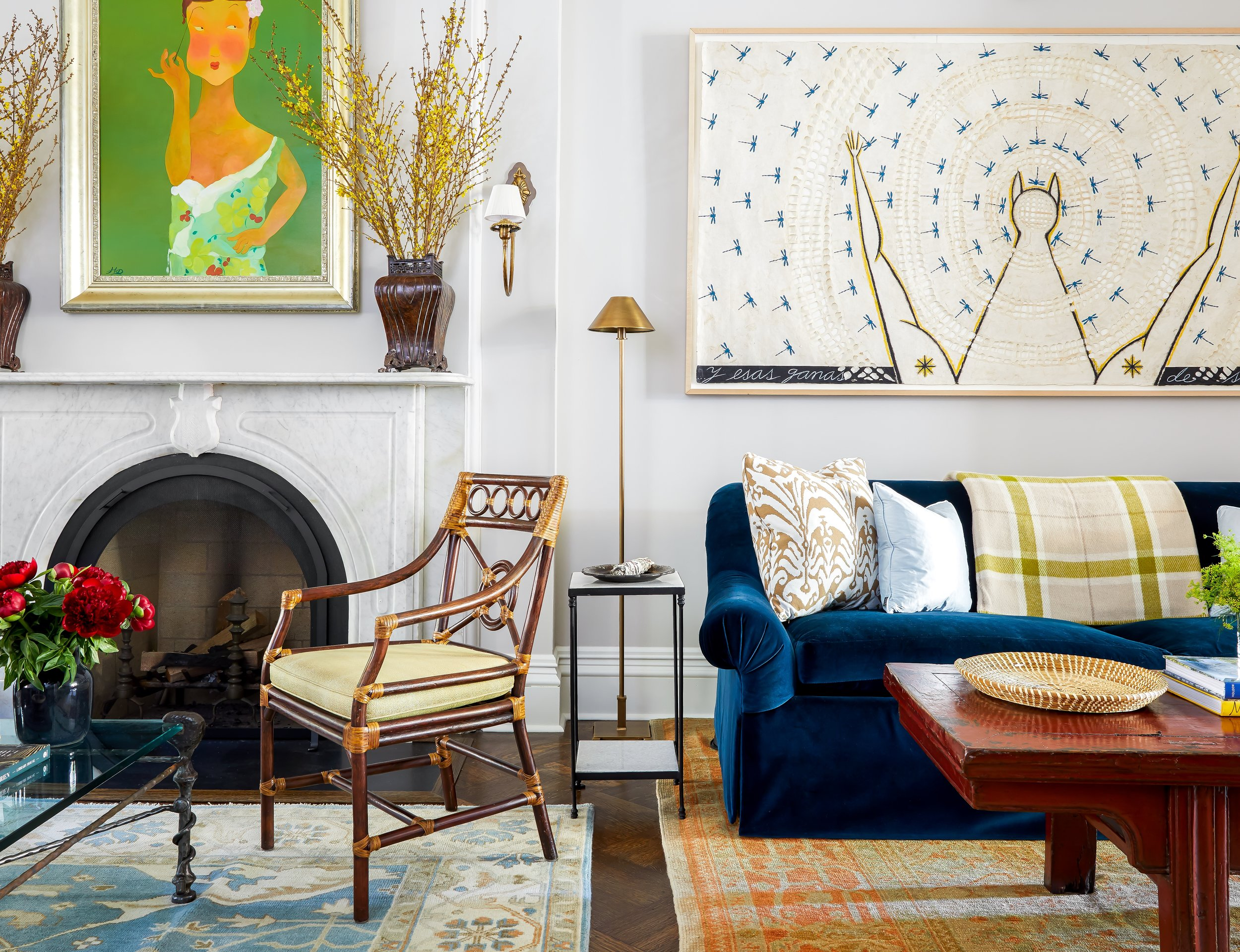 A colorful mix of antique, vintage, and custom pieces create a fun and soulful Parlor in this Brooklyn Townhouse featured in House Beautiful. An antique marble mantel was sourced to appropriately restore the character of this 1860s brownstone. A vintage iron and glass coffee table reminiscent of Giacometti sits in front one of the seven newly restored fireplaces with a vintage bamboo chair in a yellow sink from The Antique and Artisan Gallery in Stamford, CT. A custom rolled arm sofa in a plush baltic blue cotton velvet provides maximum comfort in front of an early 19th century Q'ing Dynasty Shandong Red Lacquer Tea Table from Hampton Briggs Antiques. Art by Cuban artist José Bedia.