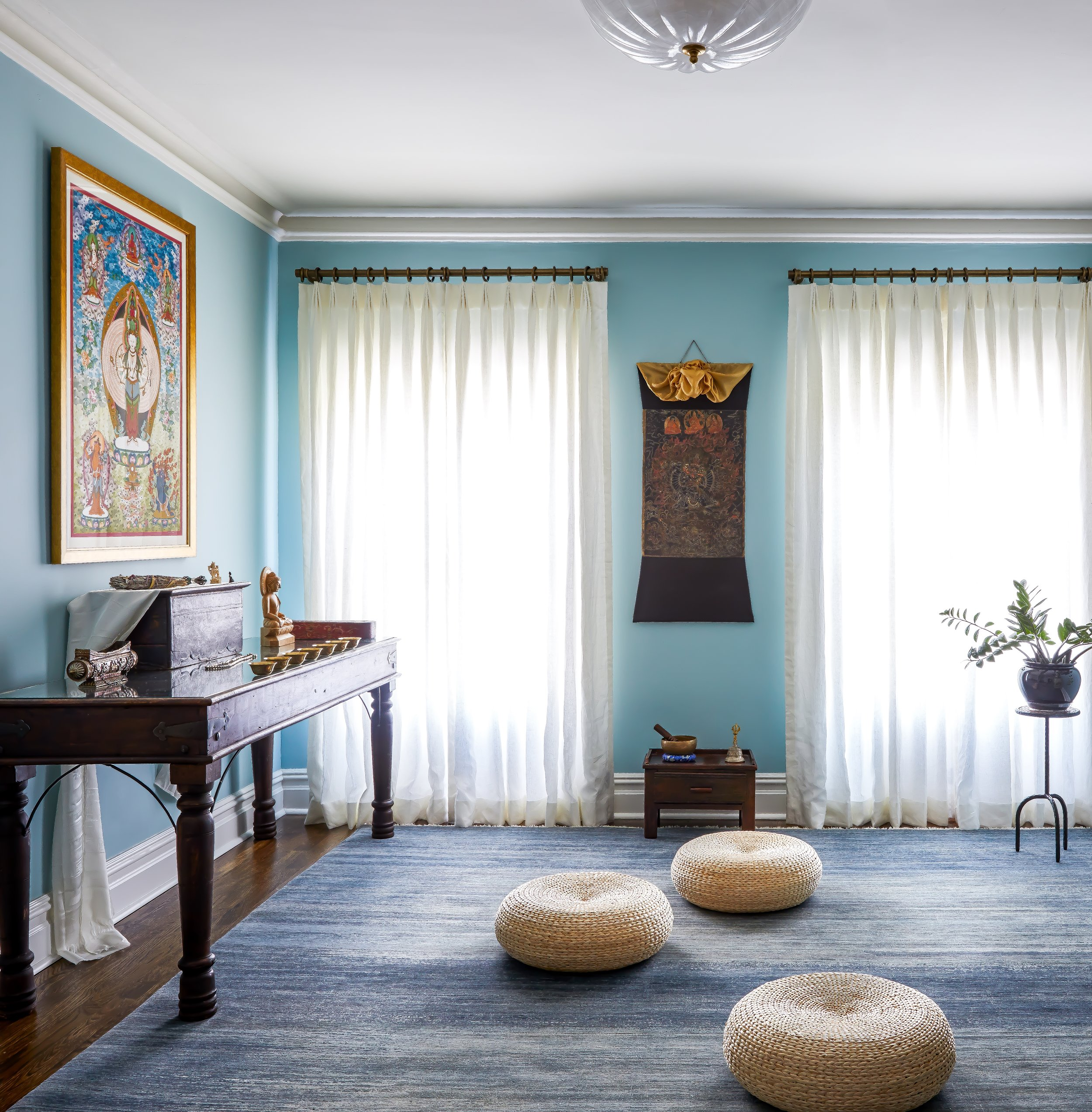 A meditation room in a Brooklyn townhouse with straw zafus, a console made from a reclaimed door, window treatments from The Shade Store in an ivory linen, and an 18th c. scroll painting - or Thangka - sourced by Leiko Coyle, an expert in South and Southeast Asian art.