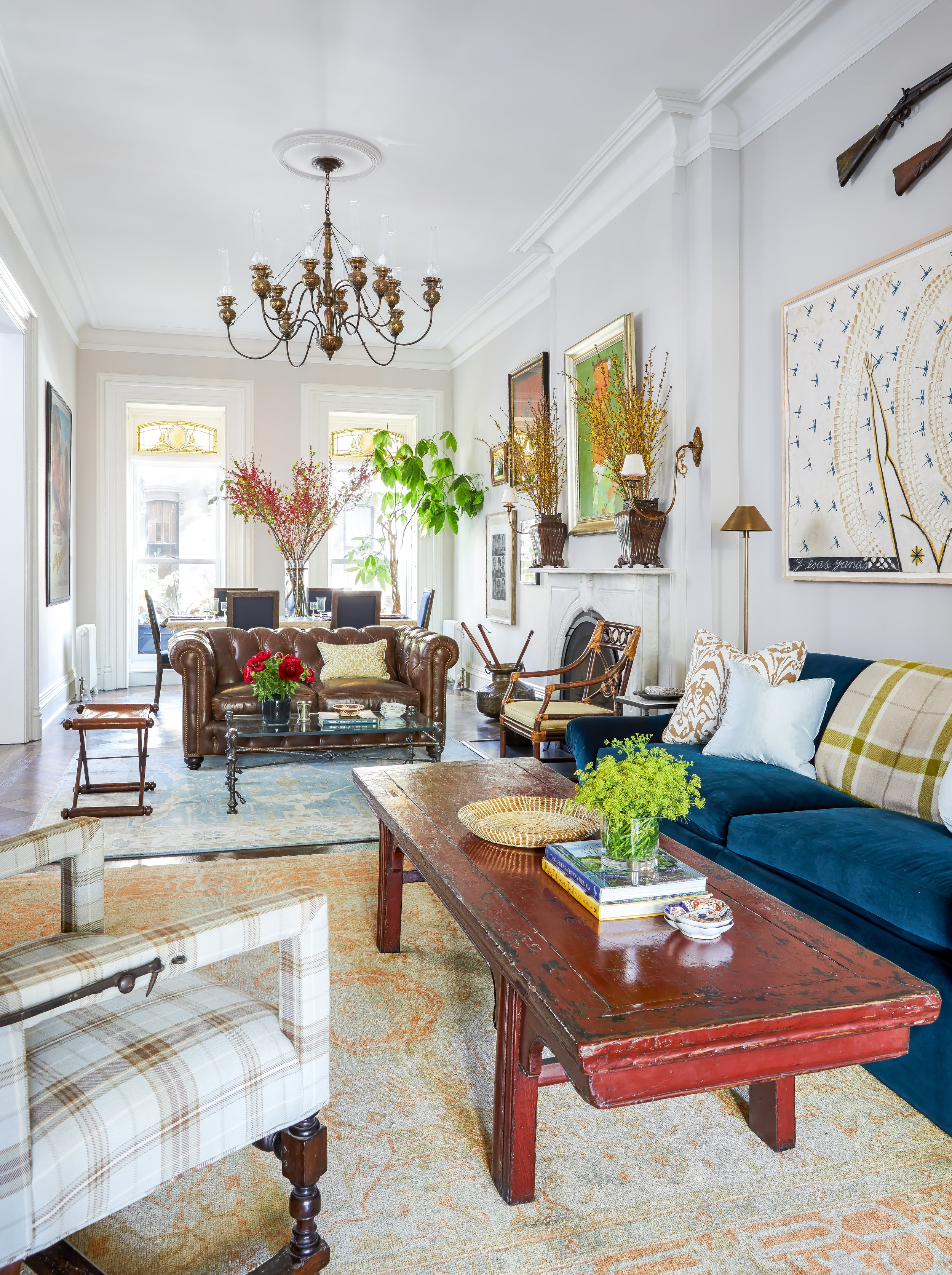 A Brooklyn Parlor in a historic townhouse in Fort Greene with a custom sofa in cotton marine blue velvet, an 18th c. antique red lacquer tea table, a plaid upholstered antique chair from John Rosselli, a custom chesterfield sofa, and a 19th c. 12-arm hand hammered brass chandelier that was converted from gas to electric.