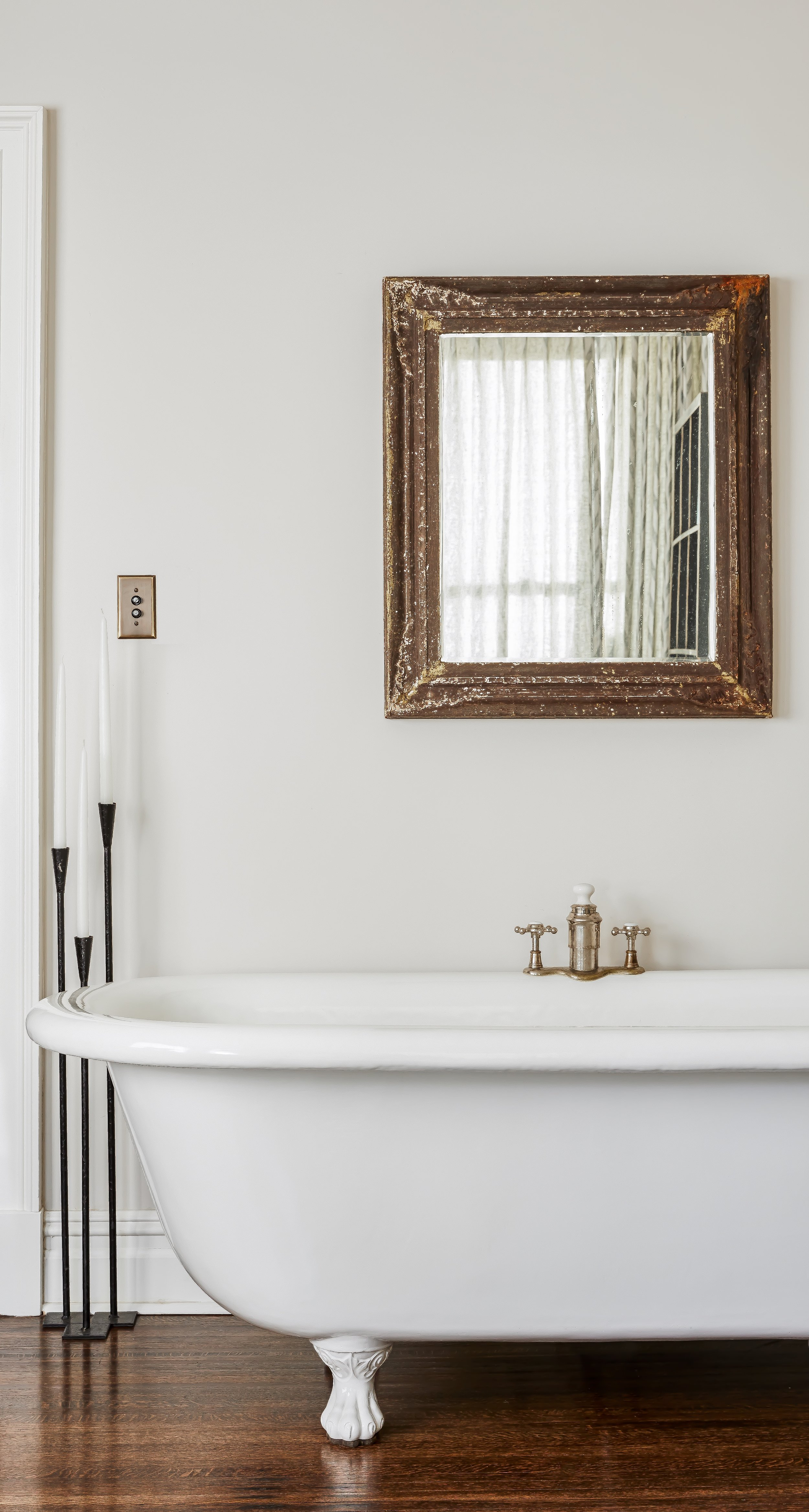 A reglazed clawfoot tub from 1870 with the original fittings replated in polished nickel, a vintage mirror from United House Wrecking, vintage iron candlesticks and a push button light switch in a Brooklyn brownstone.