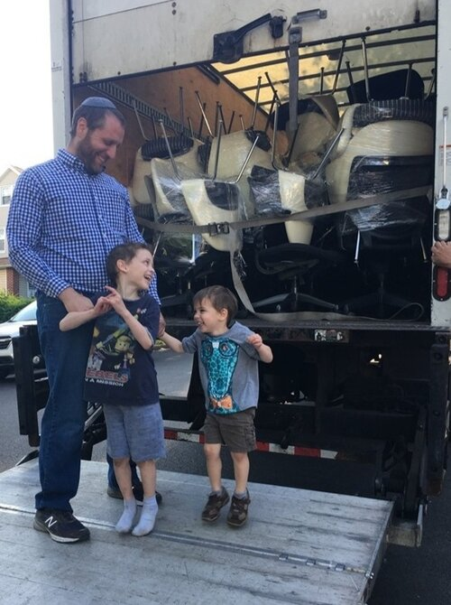 Joshua shown here, teaching some new movers how to load a truck with used Knoll Saarinen office chairs.