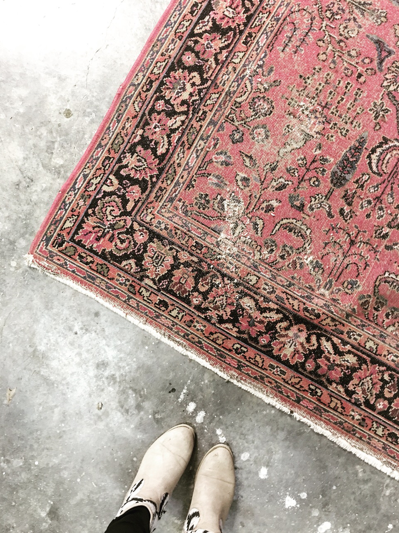 Raw image of rug in the shop being measured for an ottoman.
