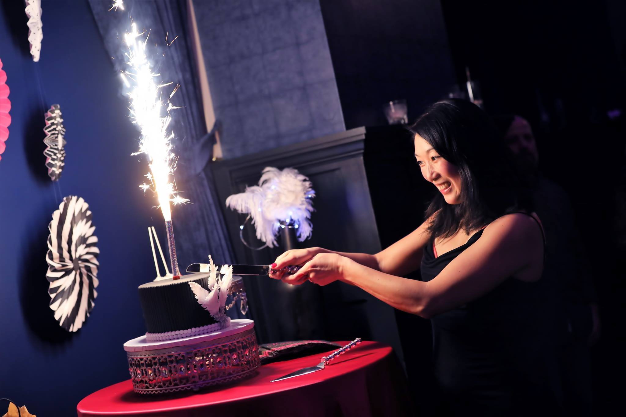A woman cutting a two-tiered black and purple cake with a sparkler on top of it.