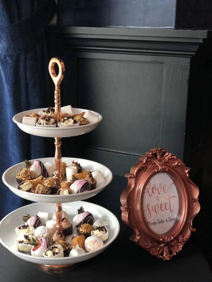 A three tiered dessert tower with white plates next to a framed love quote.