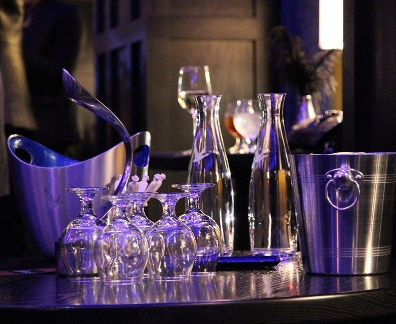 Glasses, bottles, and silver bins on a table.