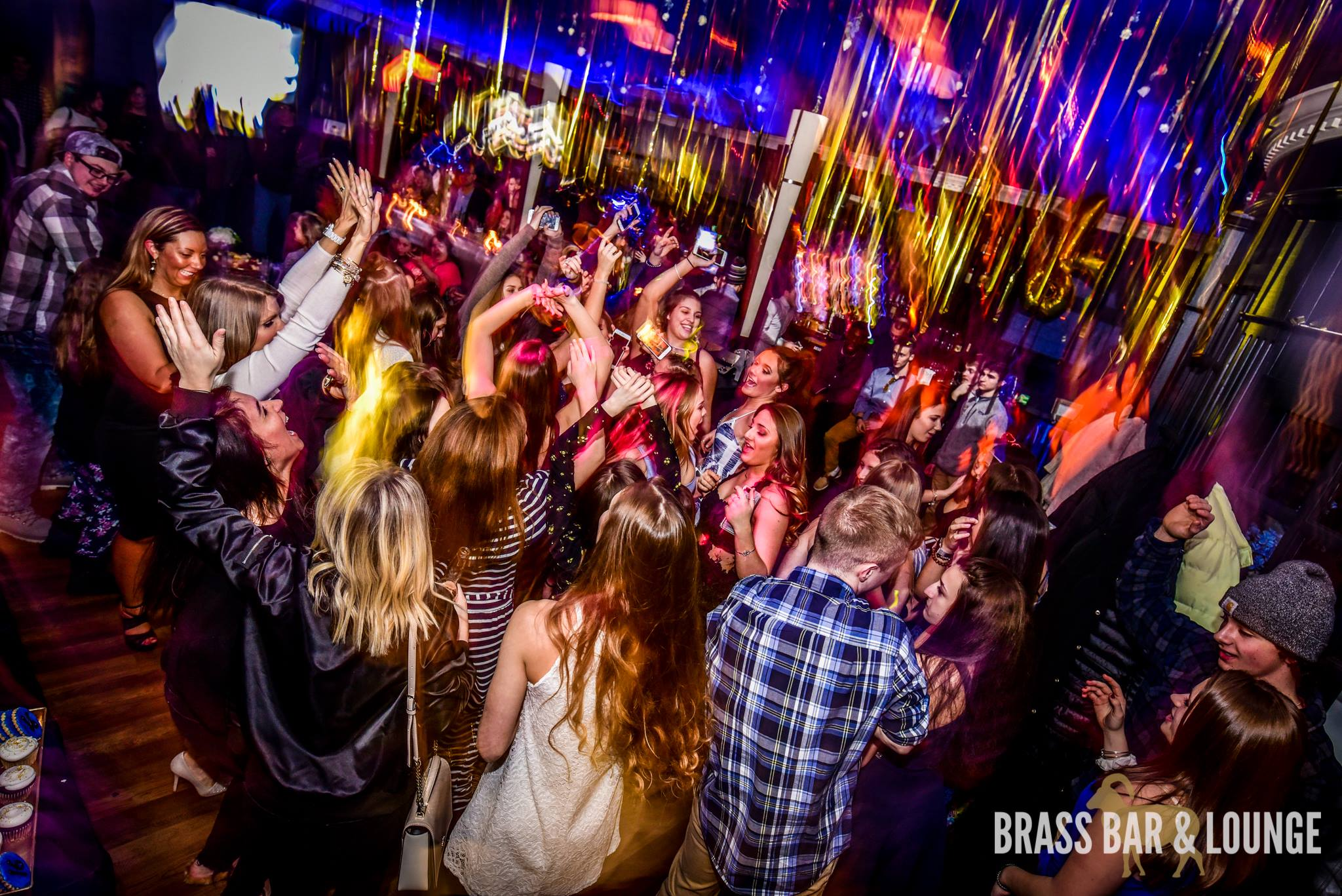 A group of people dancing with gold balloons in the background.