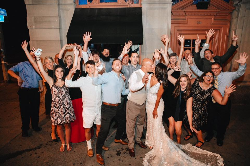 A group of people in a wedding party throwing their hands up and smiling behind the bride and groom.