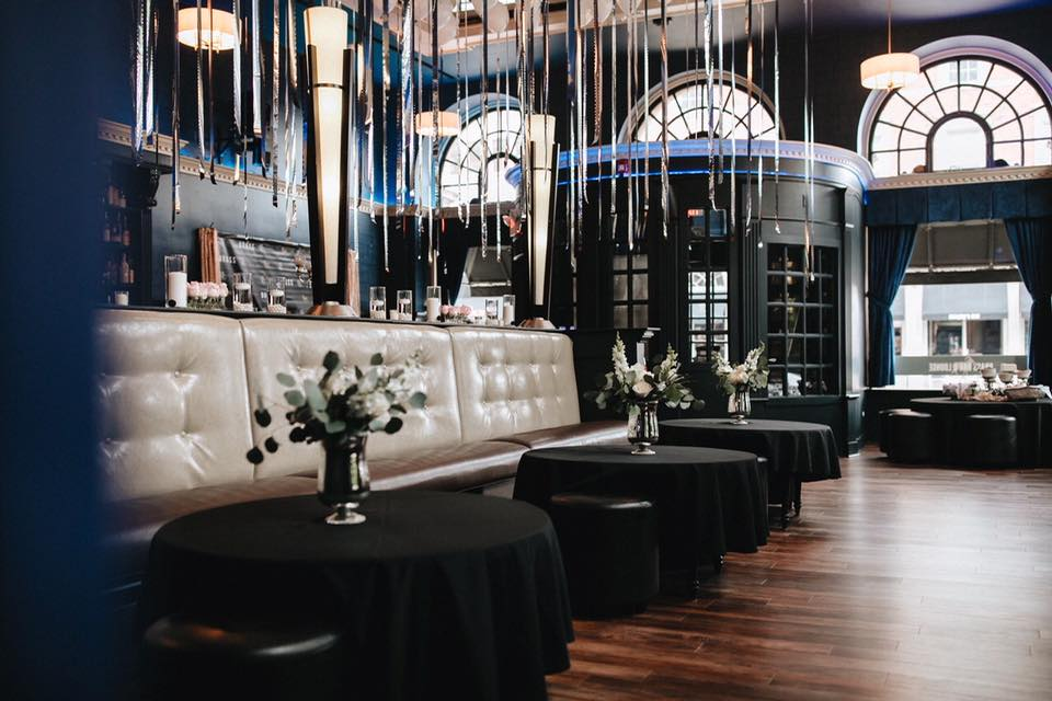 Tables in the lounge decorated with black tablecloths, white floral arrangements, and balloons hanging above.