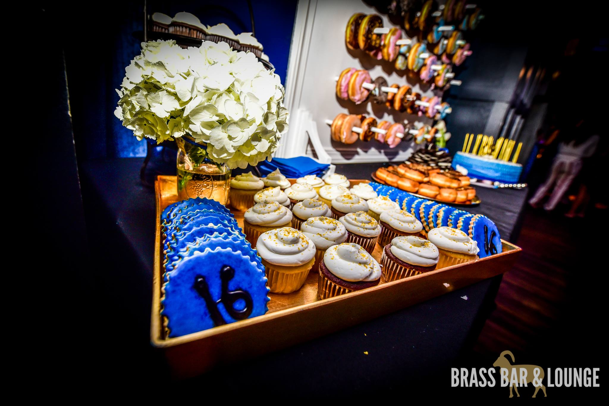A tray of desserts including blue cookies, cupcakes with white icing, and a donut wall in the background.