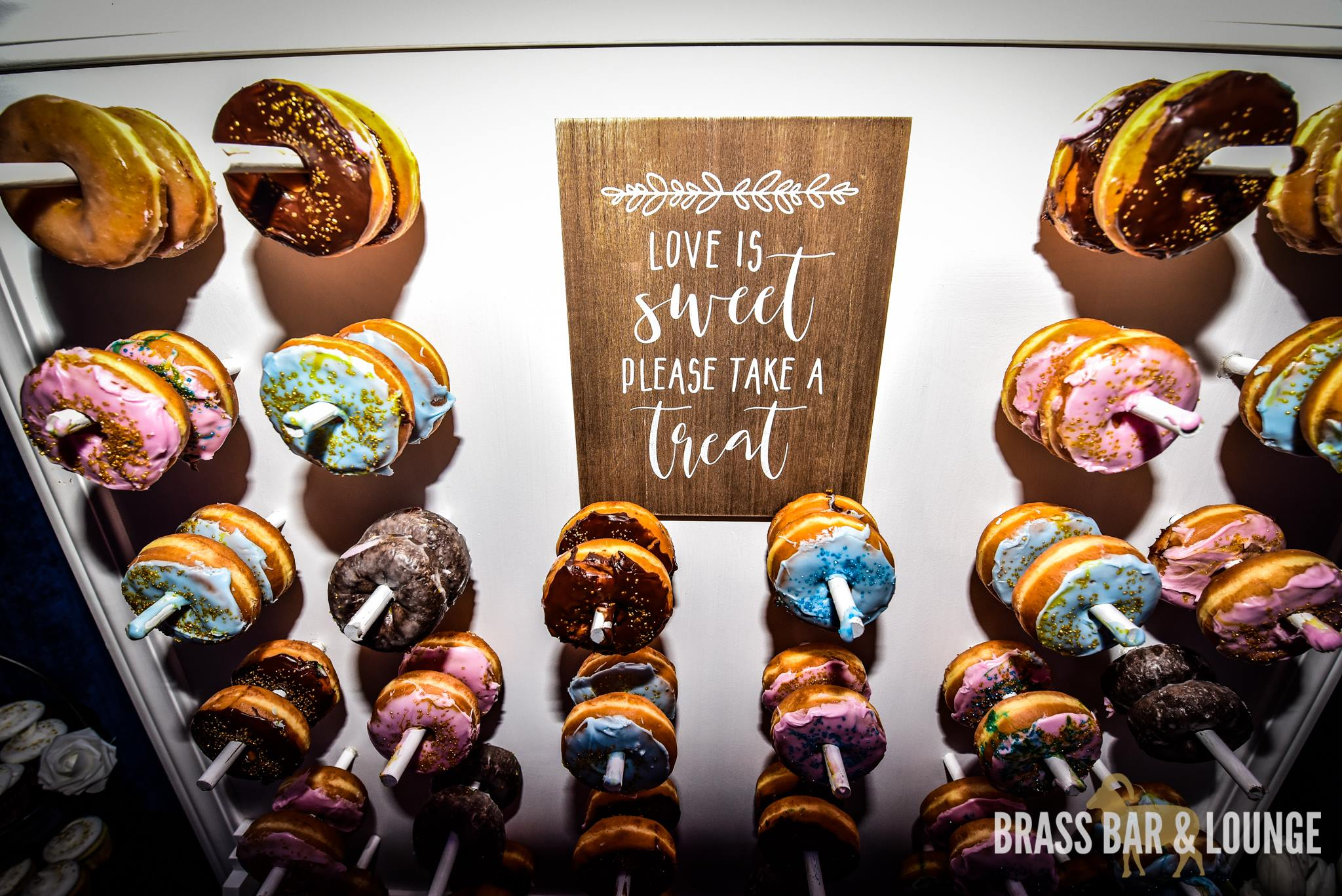 """A donut wall with a sign in the middle that reads """"Love is sweet, please take a treat."""""""