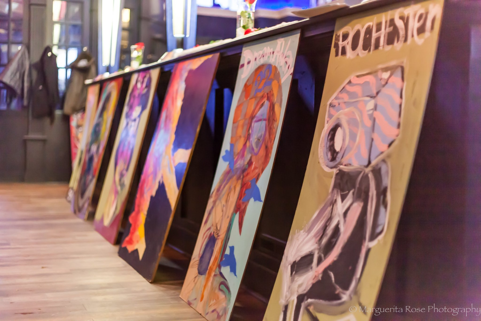A group of paintings lined up against the bottom of the bar.