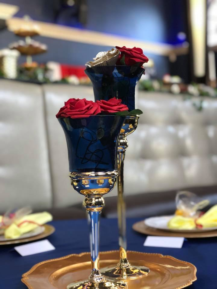 Two black glasses that are different heights filled with roses.