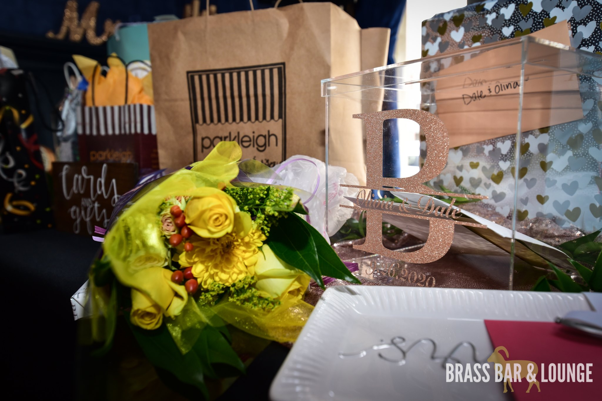 A gift table with bags and flowers.