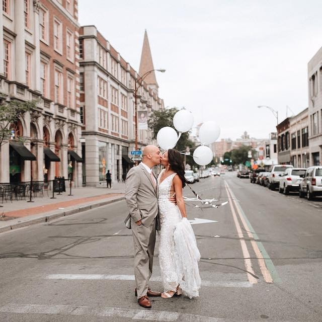 A bride and groom kissing each other in the middle of the street.