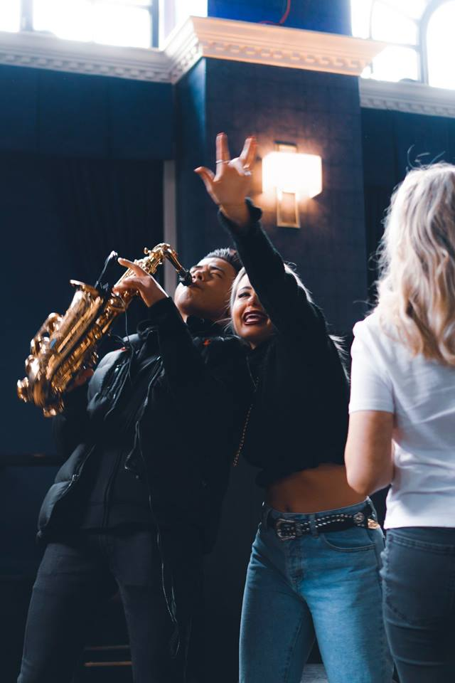 A girl grabbing the shoulder of a saxophone player.