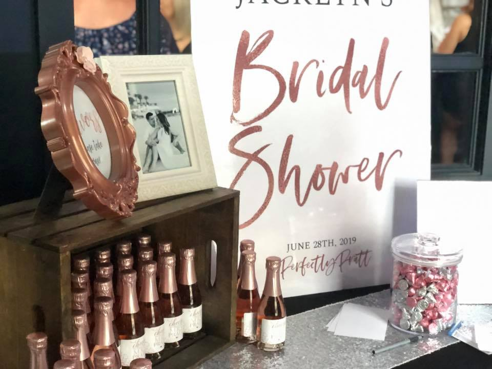 A bridal shower table setup with candy and bottles of rose.