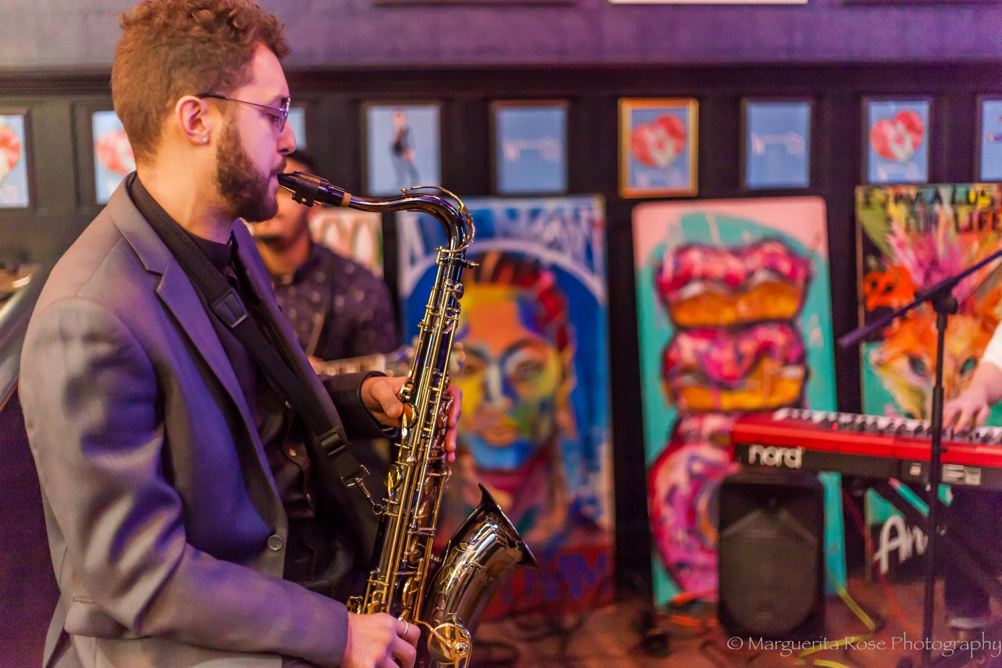 A man wearing glasses playing a saxophone with paintings and a keyboard in the background.