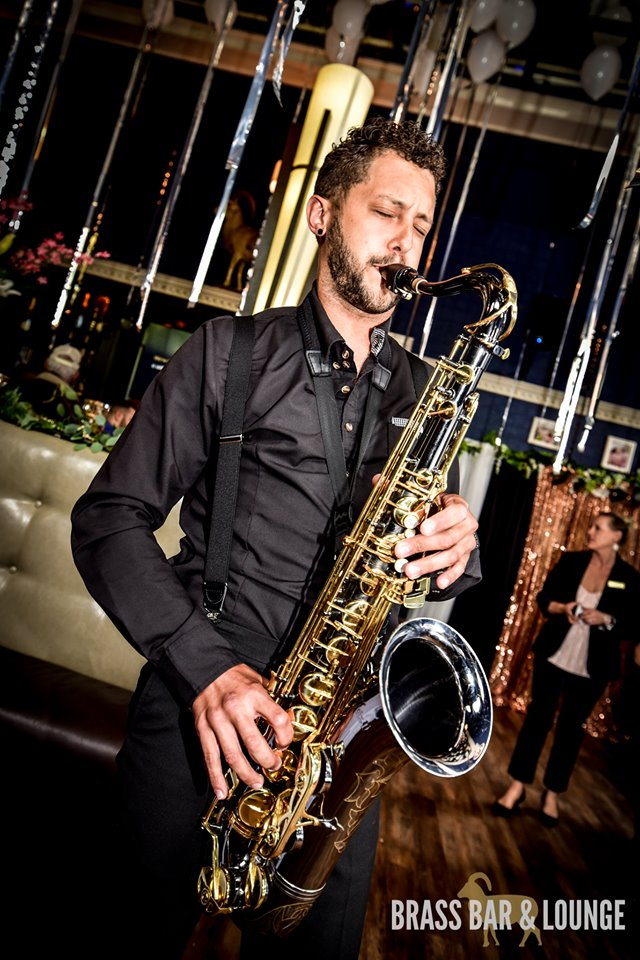 A man in a black shirt playing the saxophone.