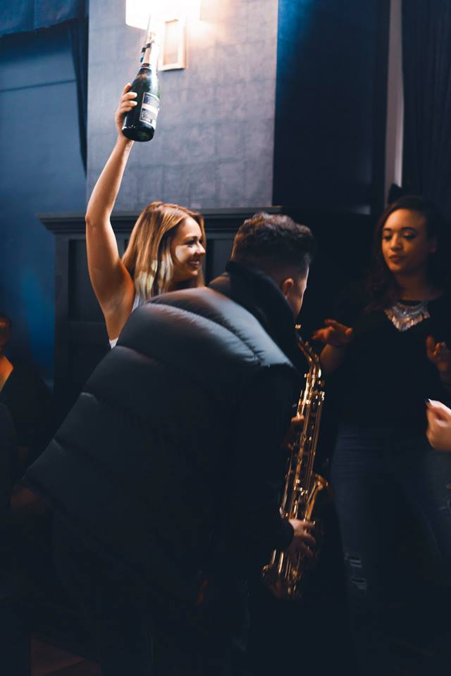 A man playing the saxophone with two girls in the background.