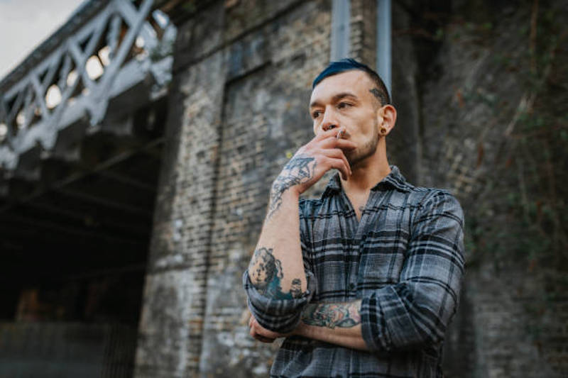 Portrait of alternative millennial man with tattoos and blue dyed hair in London, UK