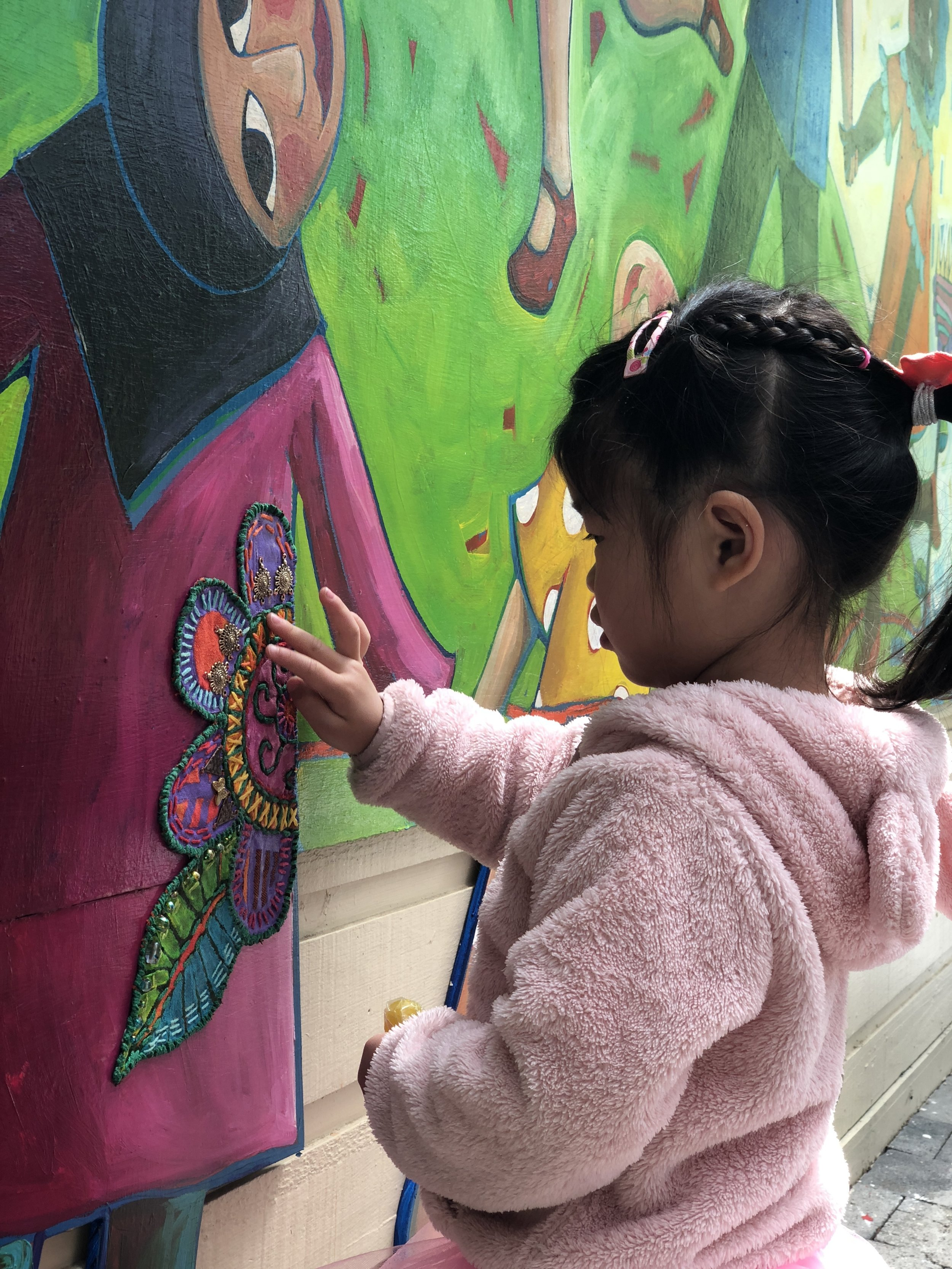 Child engaging with Sara's mural. Image courtesy the artist