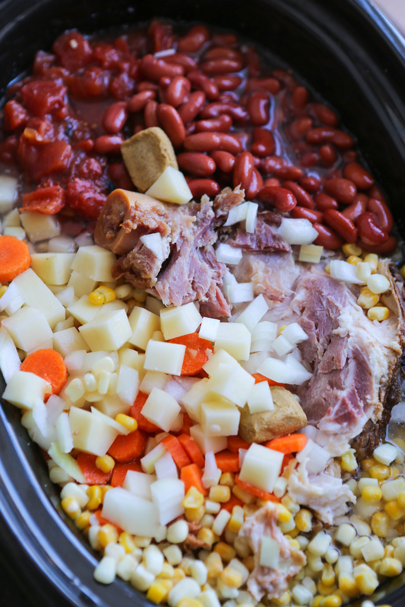 Crock pot filled with ham bone soup ingredients ready to cook