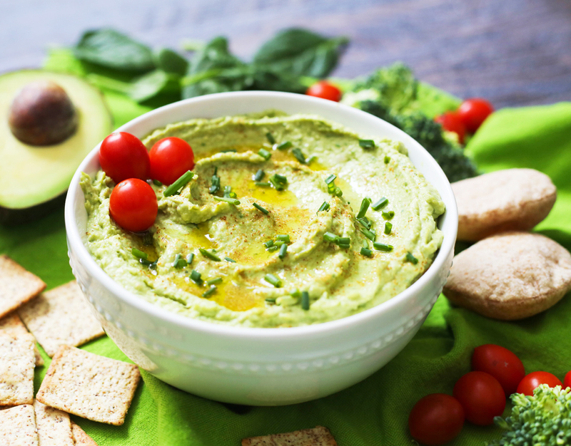 spinach hummus in a serving bowl surrounded by veggies