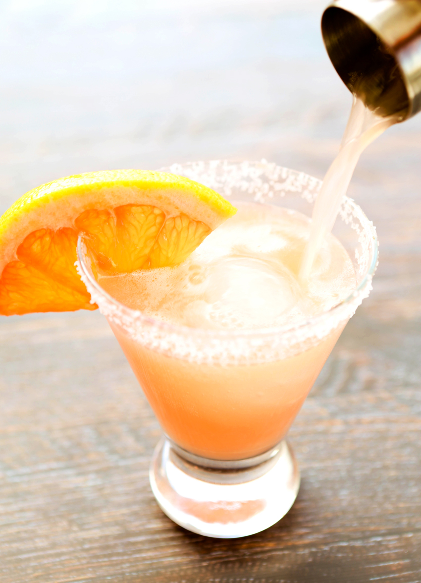 A salty dog drink being poured into a salted rimmed glass with a grapefruit rim