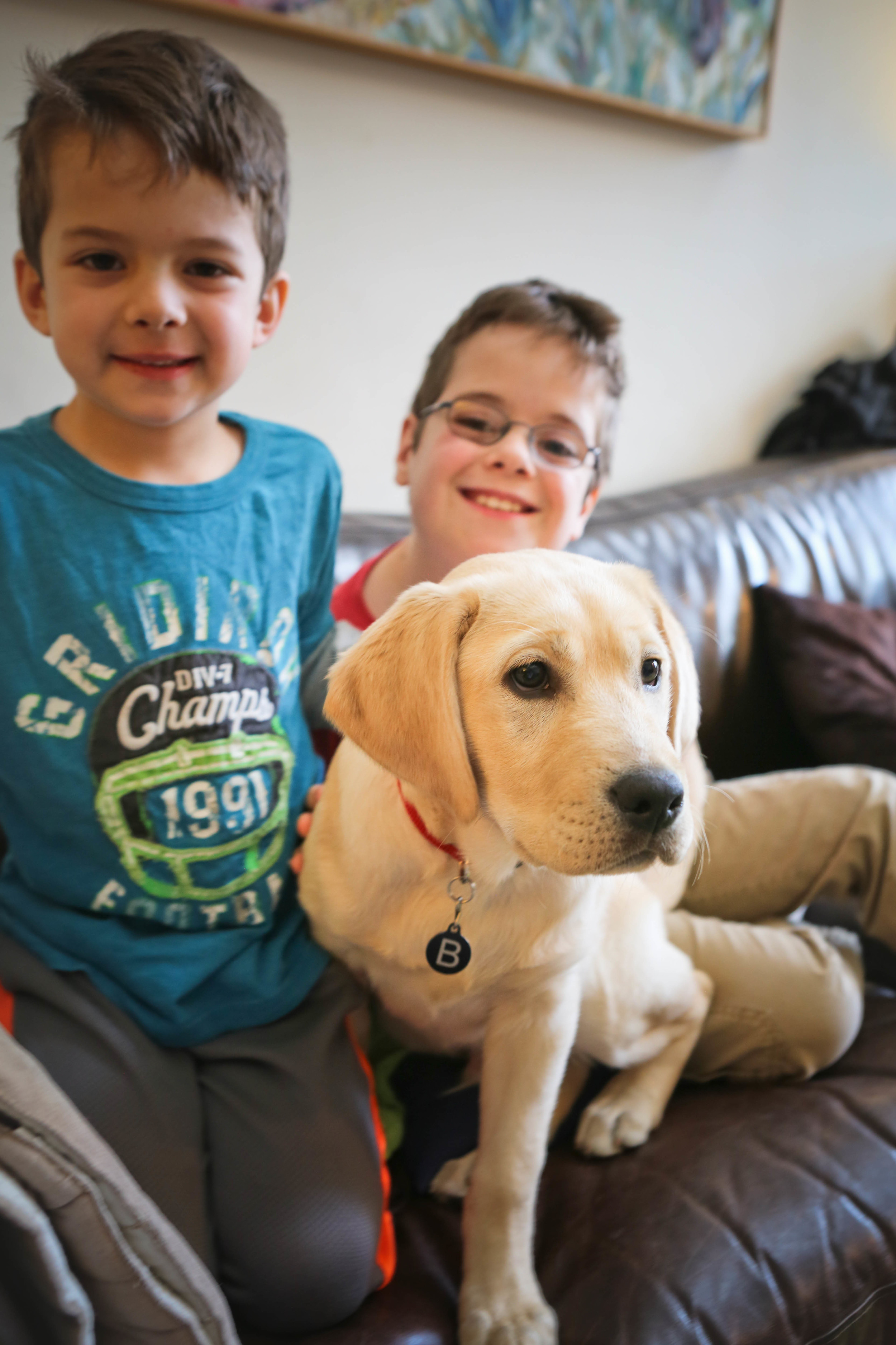 picture of 2 kids on a couch with their yellow lab puppy