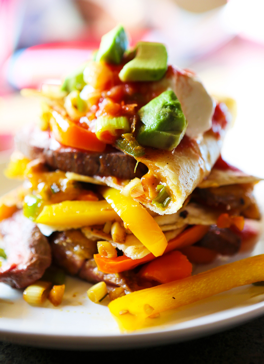 Close up of steak fajita quesadilla topped on one another with veggies and avocado spilling out.