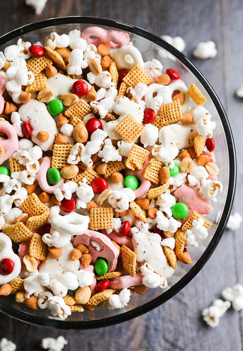 corn chex, m&m's, yogurt pretzels and popcorn mixed together in a mixing bowl